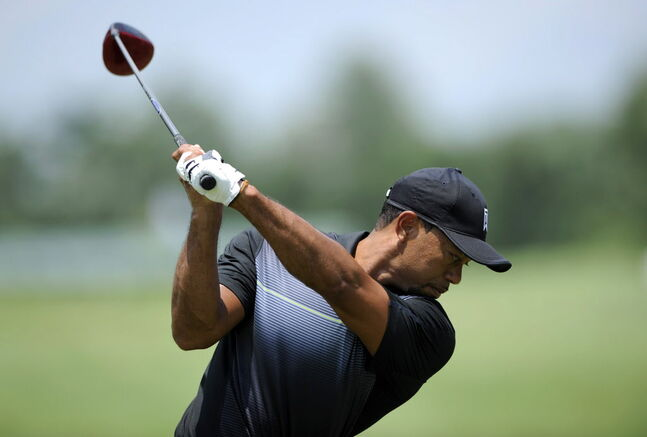 Tiger Woods takes a swing at the driving range in preparation for the Quicken Loans National golf tournament, Tuesday, June 24, 2014, in Bethesda, Md.