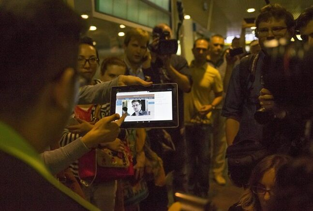 Journalists show passengers arriving from Hong Kong a tablet with a photo of Edward Snowden, a former CIA employee who leaked top-secret documents about sweeping U.S. surveillance programs, at Sheremetyevo airport, just outside Moscow, Russia, Sunday, June 23, 2013. The former National Security Agency contractor wanted by the United States for revealing two highly classified surveillance programs has been allowed to leave for a