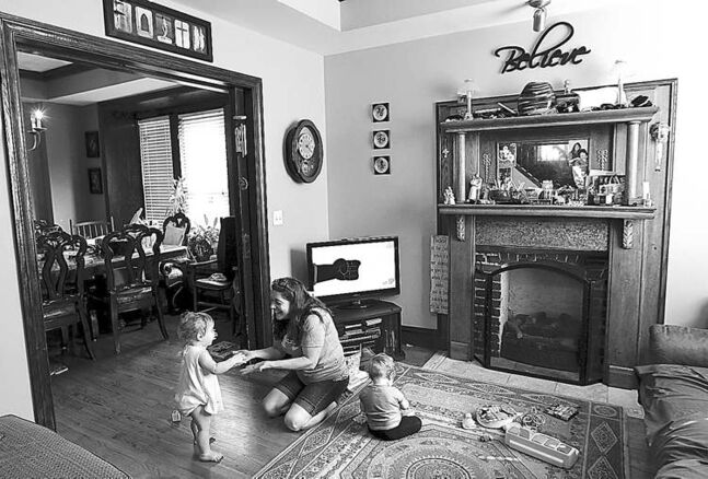 A woman plays with children in her home daycare.