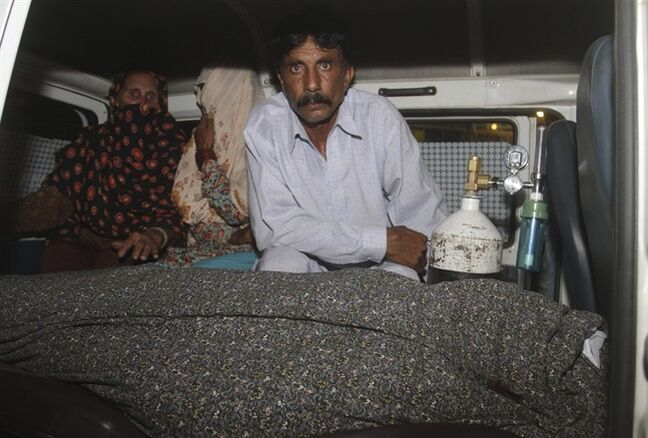 Mohammad Iqbal, right, husband of Farzana Parveen, 25, sits in an ambulance next to the body of his pregnant wife who was stoned to death by her own family, in Lahore, Pakistan, Tuesday, May 27, 2014. Nearly 20 members of the woman's family, including her father and brothers, attacked her and her husband with batons and bricks in broad daylight before a crowd of onlookers in front of the high court of Lahore, police investigator Rana Mujahid said. (AP Photo/K.M. Chaudary)