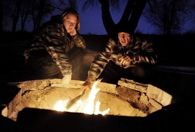 A couple warms themselves by a campfire. Once the fire is lit, keep it small, so things don't get out of control.