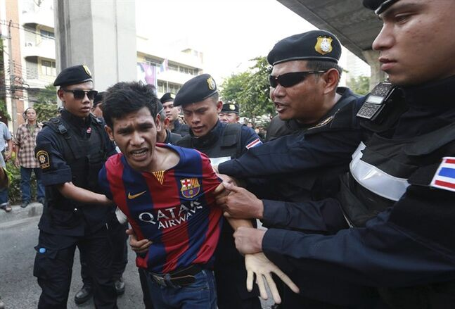 An anti-coup protester, second left, is detained by Thai police officers during a protest on a street in Bangkok, Thailand Saturday, May 24, 2014. Thailand's coup leaders said Saturday that they would keep former Prime Minister Yingluck Shinawatra, Cabinet members and anti-government protest leaders detained for up to a week to give them