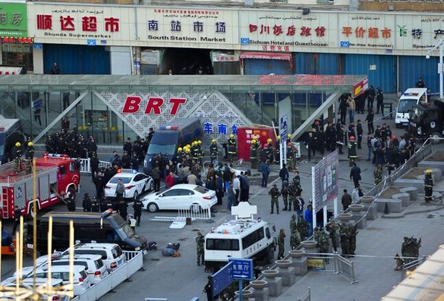 Security personnel gather near the scene of an explosion outside the Urumqi South Railway Station in Urumqi in northwest China's Xinjiang Uygur Autonomous Region on Wednesday April 30, 2014. An explosion shook the railway station in China's restive far-western region of Xinjiang, injuring many people as President Xi Jinping wrapped up a four-day visit to the area, state media said Wednesday. (AP Photo) CHINA OUT ONLINE OUT