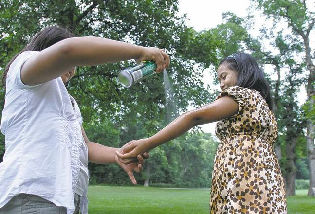 Phoebe Combis (left), 9, sprays friend Kristille Nevado, 10, with mosquito repellent at Assiniboine Park on Saturday.