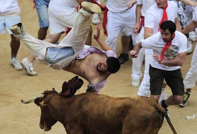 A reveler is tossed by a bull in the bull ring, at the end of third running of the bulls at the San Fermin fiestas, in Pamplona northern Spain. (AP Photo/Alvaro Barrientos)