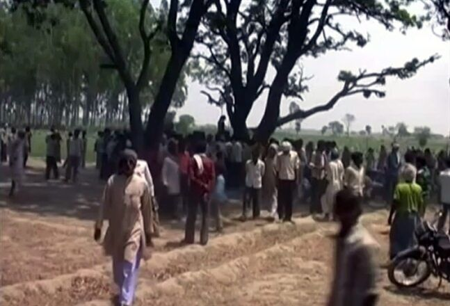 In this Wednesday, May 28, 2014 image taken from video, a crowd gathers near where two teenage sisters were found hanging from a mango tree in Katra village in Uttar Pradesh state, in northern India. Authorities have arrested three men, including two police officers, suspected of gang-raping and killing the teenagers before hanging their bodies from the tree, sparking renewed public outrage over sexual violence in the country. (AP Photo/NNIS via AP Video) INDIA OUT