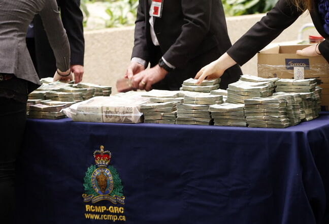 Police lay out money seized under a Manitoba law that allows the province fo confiscate the proceeds of crime.