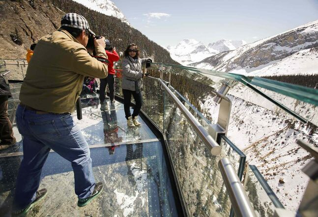 Tourists take photos from the newly opened Glacier SkyWalk in Jasper National Park. The $21-million attraction charges $24.95 per adult for access to a glass-floored observation platform that extends 30 metres above the Sunwapta Valley. The Skywalk opened to the public this month.