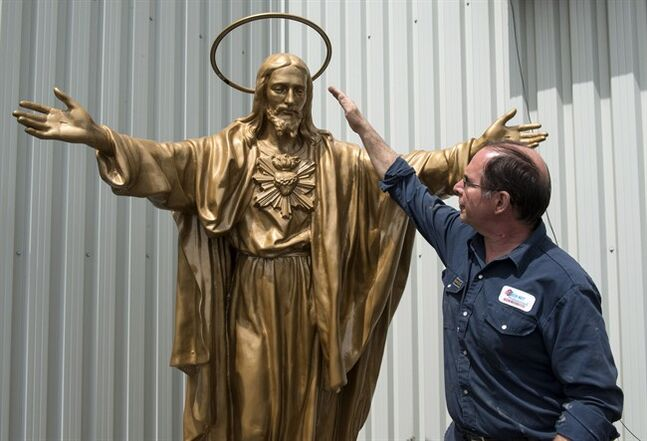 Auto body shop owner Gilles Perron looks at the restored statue of the Sacred Heart, Wednesday, June 11, 2014 in Lac-Megantic, Que. The statue, usually standing in front of the St-Agnes church, was damaged by the towering flames during last July's train derailment that killed 47 people. The statue will be replaced on its base in time for the first year anniversary celebrations. THE CANADIAN PRESS/Paul Chiasson