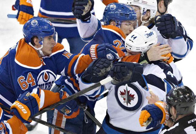Winnipeg Jets' Zach Bogosian (44) tangles with Nail Yakupov (64) and Andrew Ference (21) of the Edmonton Oilers during the third period.