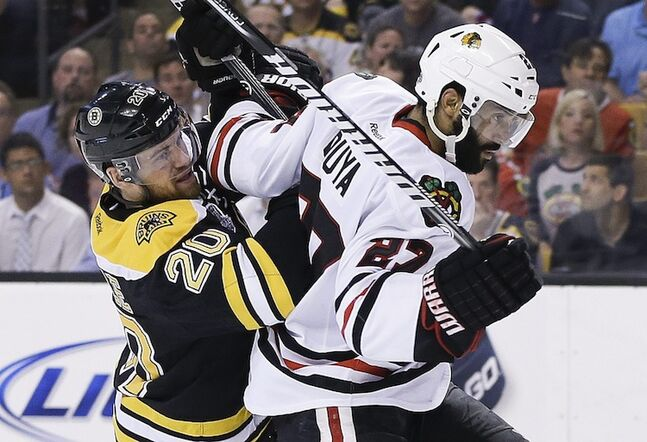 Boston Bruins left wing Daniel Paille (left) checks Chicago Blackhawks defenceman Johnny Oduya during the second period.