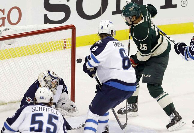 The puck glances off the glove of Minnesota Wild's Jonas Brodin (25) as he scores against Winnipeg Jets goalie Ondrej Pavelec in the first period. The goal was reviewed, and it was determined to count as a good goal.