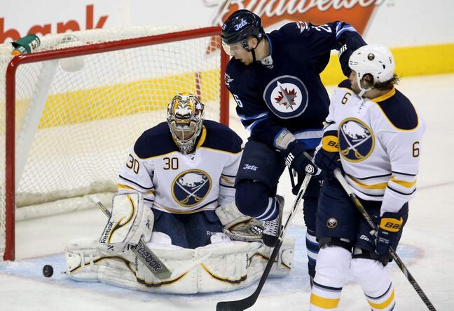 Winnipeg Jets' Blake Wheeler (26) deflects a shot just wide of Buffalo Sabres goaltender Ryan Miller (30) behind Mike Weber (6) during first period NHL hockey action in Winnipeg. 