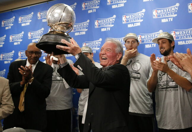 San Antonio Spurs owner Peter Holt holds up the Western Conference trophy following Game 6 of the Western Conference finals NBA basketball playoff series between the Spurs and the Oklahoma City Thunder in Oklahoma City, Saturday, May 31, 2014. San Antonio won 112-107 to advance to the NBA Finals. (AP Photo/Sue Ogrocki, Pool)