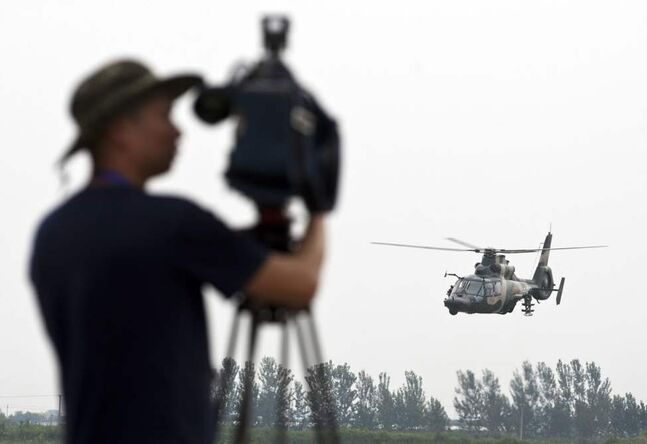 A journalist films Chinese Army Z-9WZ attack helicopter, designed and manufactured by China, during a flight demonstration for press at a Chinese People's Liberation Army base, ahead of Army Day on Aug. 1, on the outskirts of Beijing. (AP Photo/Andy Wong)