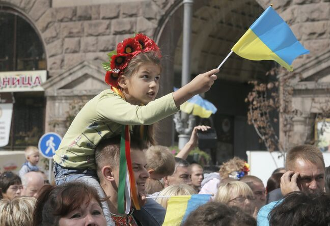 A Ukrainian girl waves the national flag sitting on her father's shoulders during celebration of Ukraine's 23rd Independence Day in Kyiv, Ukraine, Sunday.