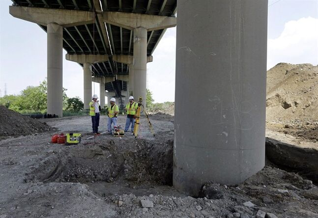 Surveyors stand near a tilting support column, front right, that is holding up the Interstate 495 bridge over the Christina River near Wilmington, Del., Tuesday, June 3, 2014, after it was closed due to the discovery of tilting support columns. The closure created heavier-than-normal traffic conditions for motorists on Interstate 95, a major East Coast artery. The bridge normally carries about 90,000 vehicles a day. (AP Photo/Patrick Semansky)