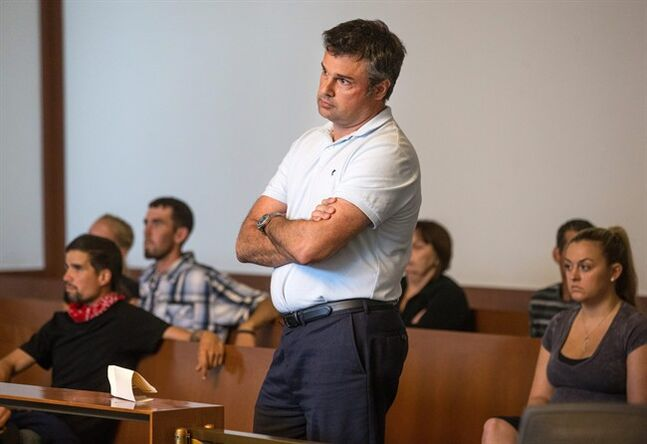 Jet Blue pilot John Manwaring stands as he is arraigned in Boston Municipal Court on a heroin possession charge Monday, July 21, 2014, in Boston. Manwaring, who listed his home as Maitland, Fla., was among six people arrested Sunday during an investigation into drug dealing near the Boston Common, Boston police said. (AP Photo/The Boston Globe, Aram Boghosian, Pool)