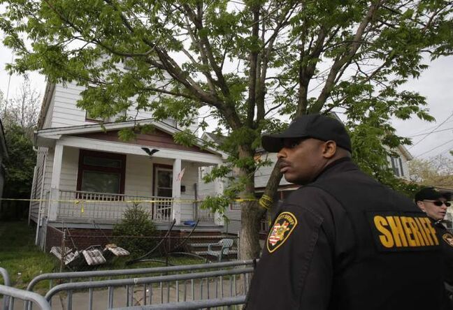 A sheriff deputy stands outside a house where three women escaped Tuesday, May 7, 2013, in Cleveland.