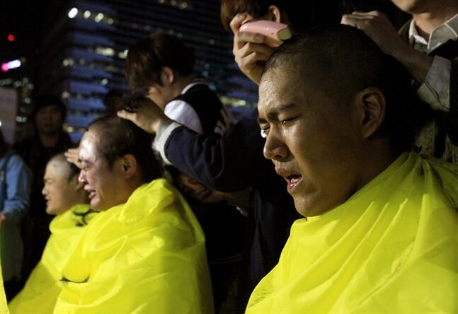 College students have their heads shaved during a rally to call for thorough investigations into the sunken ferry Sewol in Seoul, South Korea, Thursday, May 15, 2014. Prosecutors indicted the captain of the sunken South Korean ferry and three crew members on homicide charges Thursday, alleging that they failed to carry out their duties to protect passengers in need. (AP Photo/Ahn Young-joon)