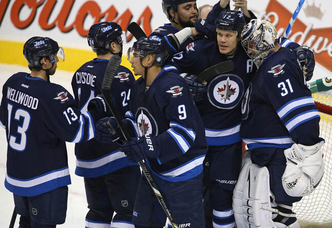 Winnipeg Jets' Kyle Wellwood (13), Grant Clitsome (24), Evander Kane (9), Dustin Byfuglien (33), Olli Jokinen (12), and goaltender Ondrej Pavelec (31) celebrate after their victory over the Pittsburgh Penguins' at MTS Centre, Friday, January 25, 2013.