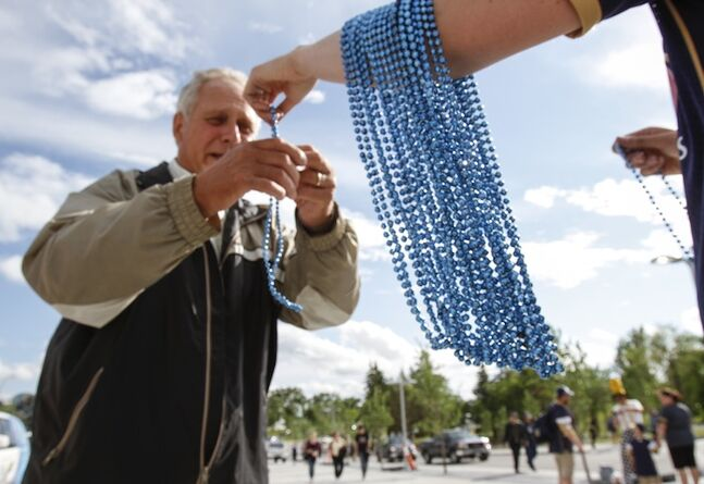 A Winnipeg Blue Bomber fan gets a string of blue beads on the way in to Investors Group Field.