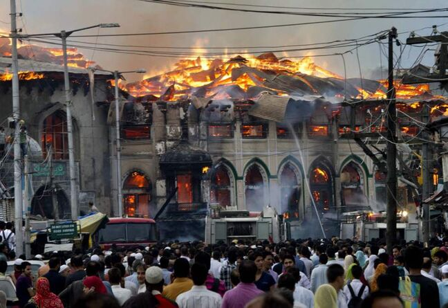 Kashmiri residents watch as firefighters try to extinguish a fire at the nearly 200-years-old Sheikh Abdul Qadir Jeelani Shrine, popularly known as Ghaus-e-Azam, or Dastgeer Sahab, in downtown Srinagar, India. Anti-India clashes between protesters and government forces erupted in the main city in Indian-controlled Kashmir Monday after the highly revered Muslim shrine was destroyed in the fire, police said. The cause of the fire is yet unknown. (AP Photo/Dar Yasin)