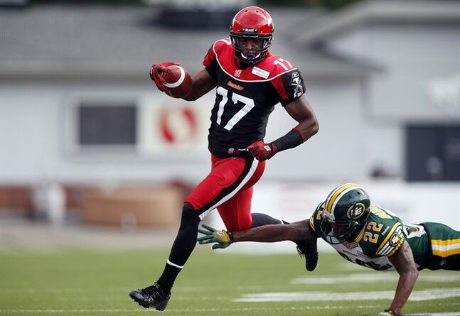 Calgary Stampeders' Maurice Price evades Edmonton Eskimos' Joe Burnett to score a touchdown during first half CFL football action in Calgary on Sept. 2, 2013. The Canadian Football League fined Calgary Stampeders receiver Maurice Price on Tuesday for making