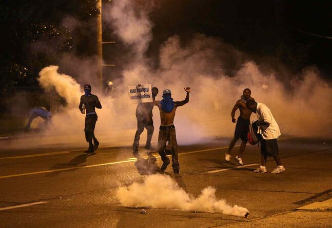 People protest as tear gas canisters detonate around them on Wednesday, Aug. 13, 2014, in Ferguson, Mo. Protests in the St. Louis suburb rocked by racial unrest since a white police officer shot an unarmed black teenager to death turned violent Wednesday night, with people lobbing molotov cocktails at police who responded with smoke bombs and tear gas to disperse the crowd. (AP Photo/St. Louis Post-Dispatch, Chris Lee)