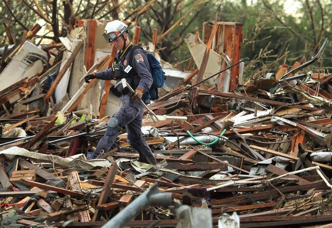 A member of Nebraska Task Force-1 walks through the debris of a home along SW 6th Street in Moore, Okla., on Tuesday.