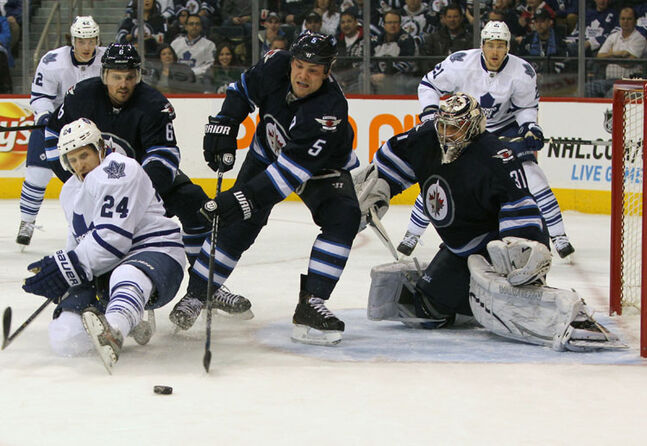 Winnipeg Jets defenceman Mark Stuart (5) defends the net as Toronto Maple Leafs player John-Michael Liles is knocked down by Jets defenceman Ron Hainsey during NHL action at the MTS Centre Thursday.