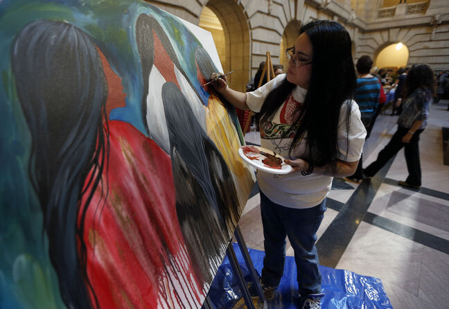 Jackie Traverse paints a work of art at the legislature on Friday, at a luncheon in anticipation of International Women's Day today.