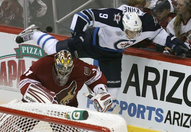 Winnipeg Jets' Evander Kane, top, flies over Phoenix Coyotes goaltender Mike Smith during the third period at the Jobing.com Arena in Glendale, Arizona.  The Coyotes beat the Winnipeg Jets 4-1.   (JOE BRYKSA / WINNIPEG FREE PRESS)