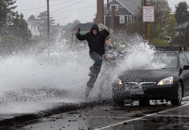Caleb Lavoie, 17, of Dayton, Maine, front, and Curtis Huard, 16, of Arundel, Maine, leap out of the way as a large wave crashes over a seawall on the Atlantic Ocean during the early stages of Hurricane Sandy, in Kennebunk, Maine. (AP Photo/Robert F. Bukaty)