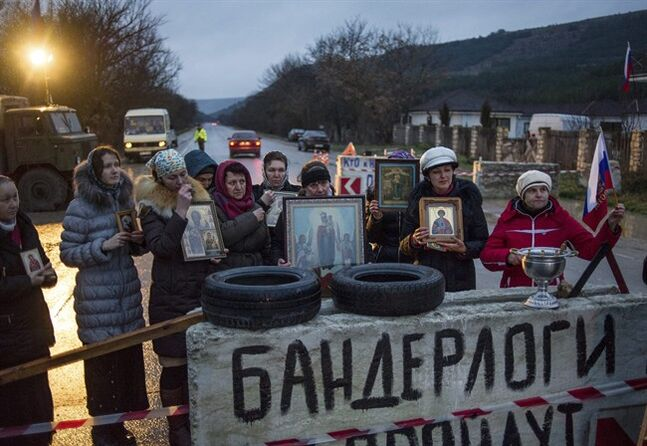Pro-Russian activists hold up Orthodox icons at a checkpoint outside the Ukrainian Black Sea port of Sevastopol in the Crimea, Ukraine, Thursday, Feb. 27, 2014. The banner reads