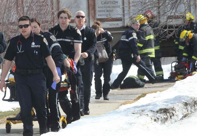 A victim from the collision between a train and a vehicle at Beaverhill Boulevard on the CP line is rushed to an ambulance Wednesday.