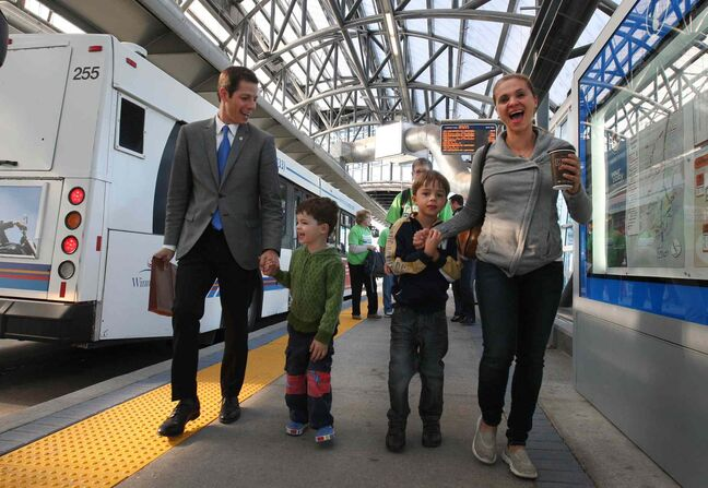 Brian Bowman arrives on a bus at the Osborne rapid transit station Tuesday morning with his family: wife Tracy, and his two sons, Austin, left, and Hayden. He announced he would get all phases of rapid transit completed in Winnipeg by 2030.