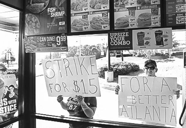Protesters press signs to the window of an Atlanta Church's Chicken during a walkout of fast-food workers in the U.S.