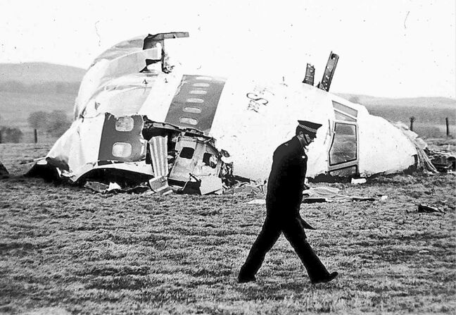 A police officer walks by the nose of Pan Am flight 103 in a field near the town of  Lockerbie, Scotland, in December 1988. The crash killed 270 people.