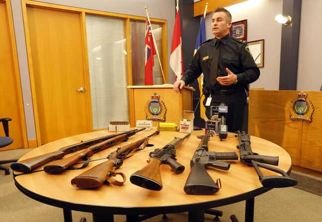 Const. Jason Michalyshen displays some of the seized drugs and guns from two residences in the 500 block of Chalmers Avenue.