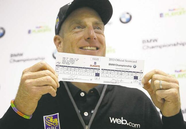 Jim Furyk holds up his second-round scorecard at the BMW Championship tournament at Conway Farms Golf Club in Lake Forest, Ill.