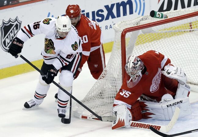 Detroit Red Wings goalie Jimmy Howard stops Chicago Blackhawks center Michal Handzus during the second period.