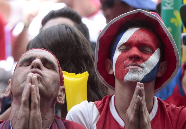 Costa Rica soccer fans pray while they attend a live telecast of the World Cup quarterfinal between Costa Rica and Netherlands, inside a park in San Jose, Costa Rica, Saturday, July 5, 2014.