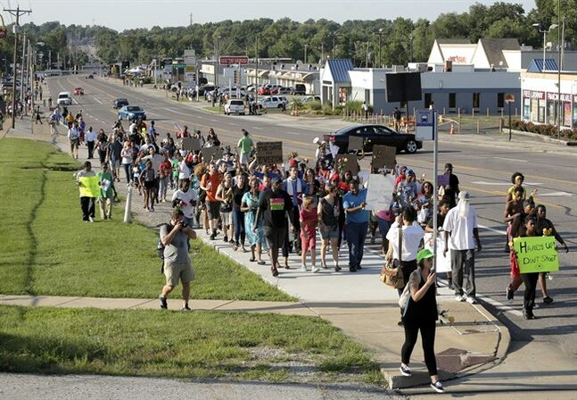 Protesters march Tuesday, Aug. 19, 2014, for Michael Brown, who was killed by police Aug. 9 in Ferguson, Mo. Ferguson's leaders urged residents Tuesday to stay home after dark to