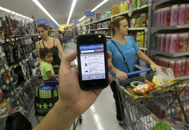 """FILE - In this Sept. 19, 2013 file photo, a Wal-mart representative demonstrates the now-discontinued Scan & Go mobile application on a smartphone at a Wal-mart store in San Jose, Calif. Instead of looking at the app as a failure, Wal-Mart took what it learned from """"Scan & Go"""" to create another service: It found that customers like being able to track their spending, an insight that became the impetus for a program that enables shoppers to see their buying habits by storing electronic receipts. (AP Photo/Jeff Chiu, File)"""
