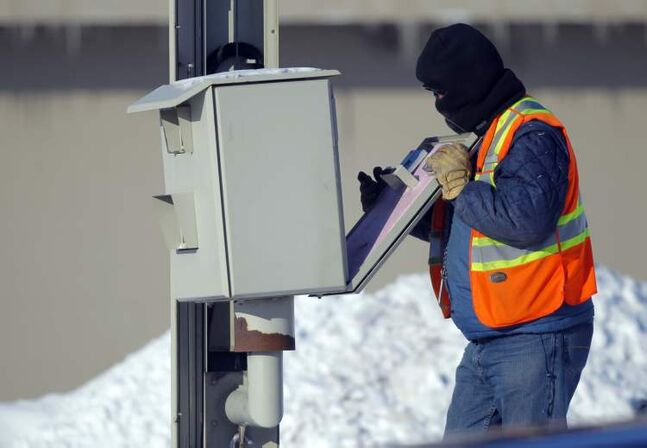 A contract worker for the City of Winnipeg services a red light camera on Panet Road. He did not want to give his name but told the photographer he moved to Winnipeg from Africa eight years ago and was used to 41 C temperatures.
