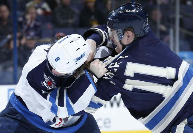 Blue Jackets left wing Matt Calvert (right) and Jets defenseman Jacob Trouba exchange blows during the first period Monday night.