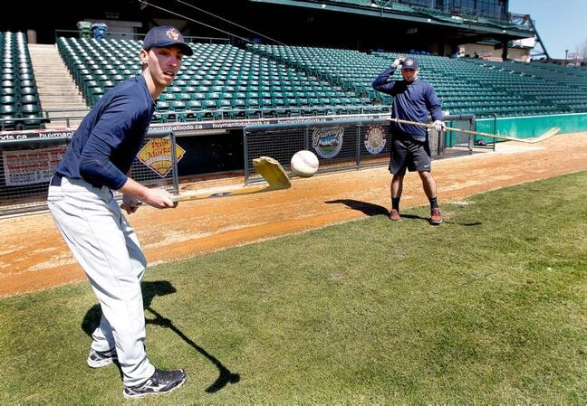 Pitcher Chris Kissock and outfielder Tim Smith  show off their hockey skills at Shaw Park on Friday. Goldeyes training camp opens today.