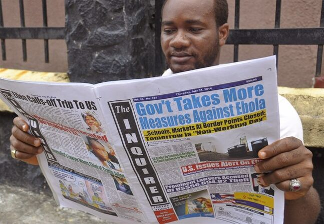 A man reads a newspaper with headlines reading 'Gov't Takes More Measures Against Ebola, as fear about the virus spread in the city of Monrovia, Liberia, Thursday, July 31, 2014. The worst recorded Ebola outbreak in history surpassed 700 deaths in West Africa as the World Health Organization on Thursday announced dozens of new fatalities. (AP Photo/Abbas Dulleh)