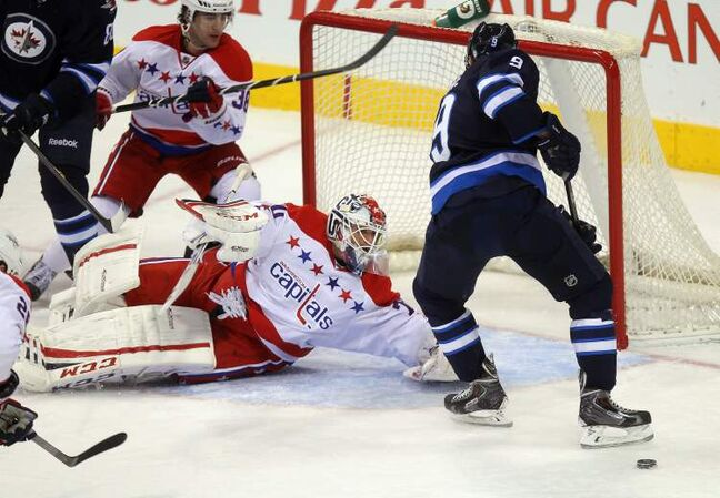 Winnipeg Jets forward Evander Kane loses the puck in his skates as Washington Capitals goaltender Braden Holtby sprawls out to cover the net during the first-period.